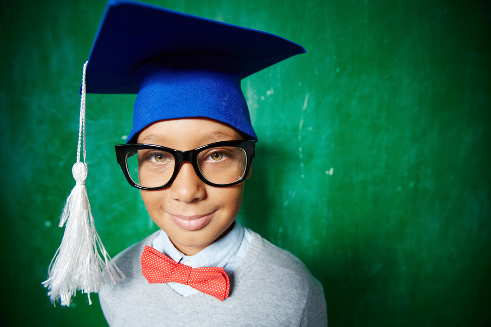 Elementary Learner In Eyeglasses And Graduation Hat Looking At Camera With Smile