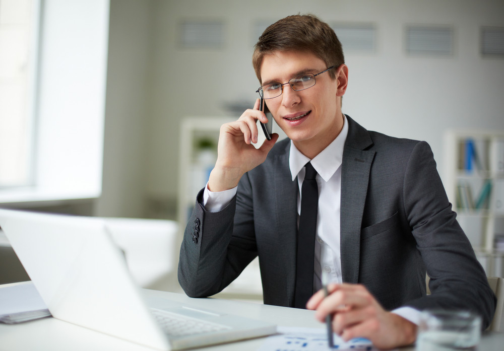Young Businessman In Suit Looking At Camera While Calling In Office