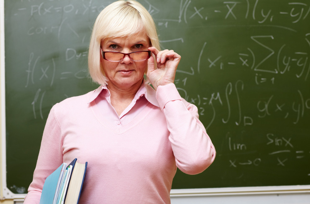 Portrait Of An Elegant Senior Lady Standing Near The Blackboard And Looking Strictly At Camera