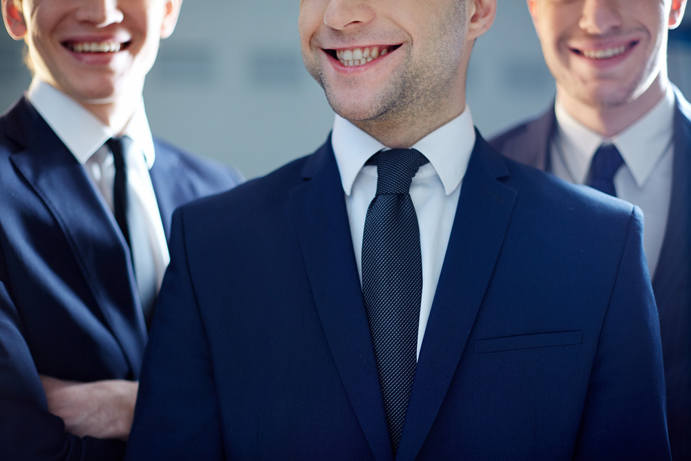 Cropped Image Of A Ceo Grinning From Ear To Ear Being On The Foreground