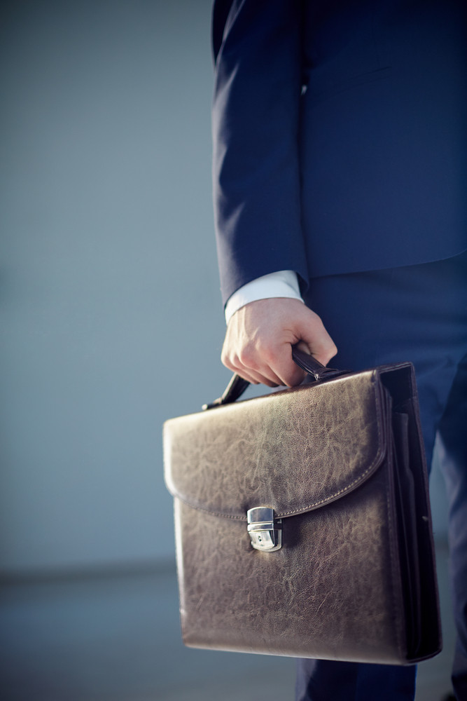 Vertical Cropped Image Of A Businessperson Carrying A Leather Briefcase Isolated On Grey