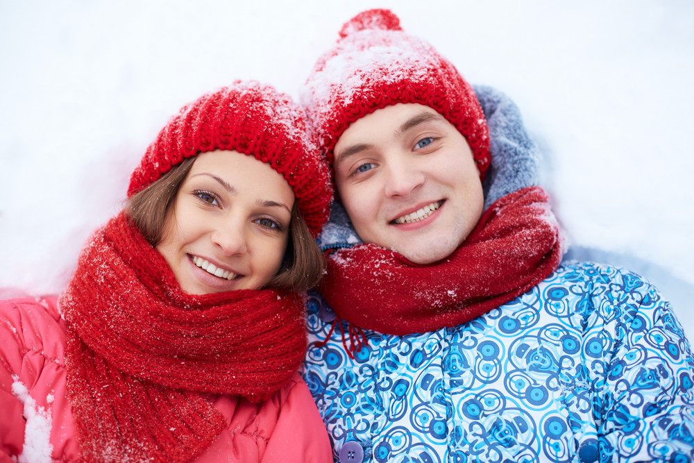 Portrait Of Happy Couple In Winterwear Lying On Snow And Looking At Camera