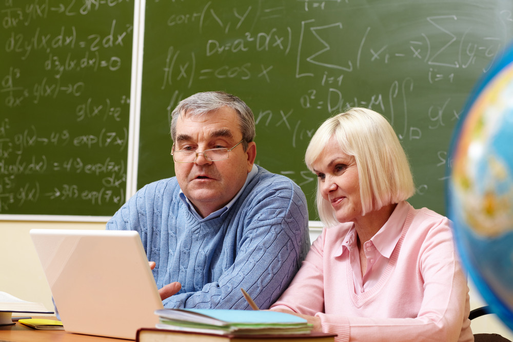 Portrait Of Mature Man And Aged Female Working With Laptop In Classroom