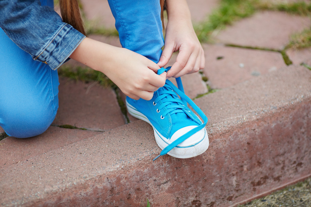 Hands Of Little Girl Tying Lace Of Her Shoe Outside