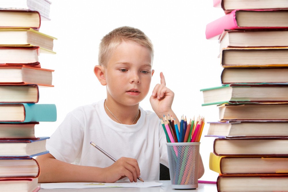 Portrait Of Cute Youngster Sitting Among Stacks Of Books And Thinking While Drawing