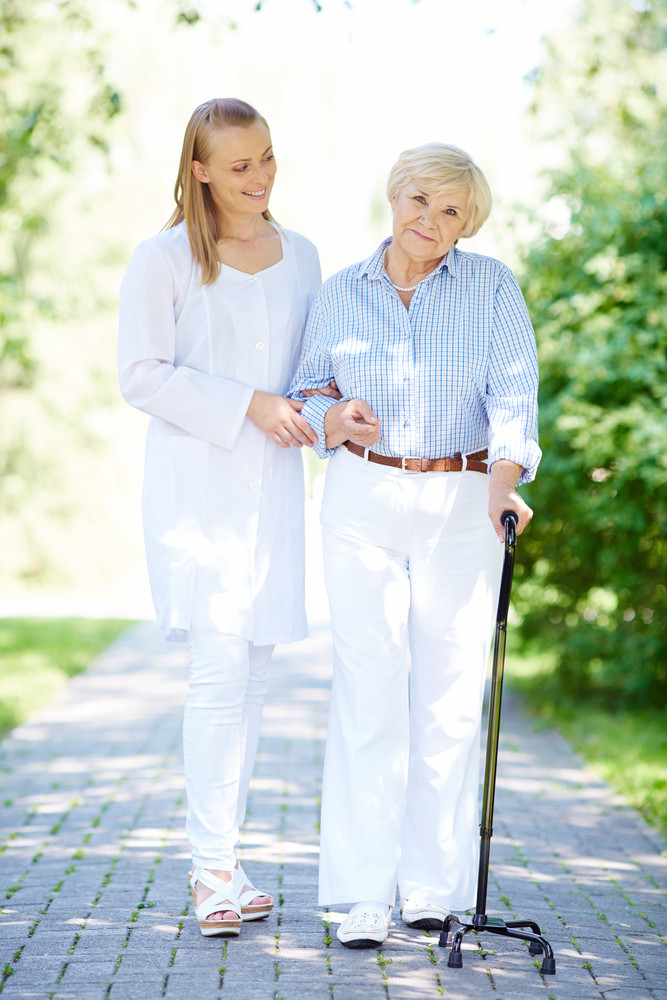 Pretty Nurse And Senior Patient With Walking Stick Having A Walk In Park
