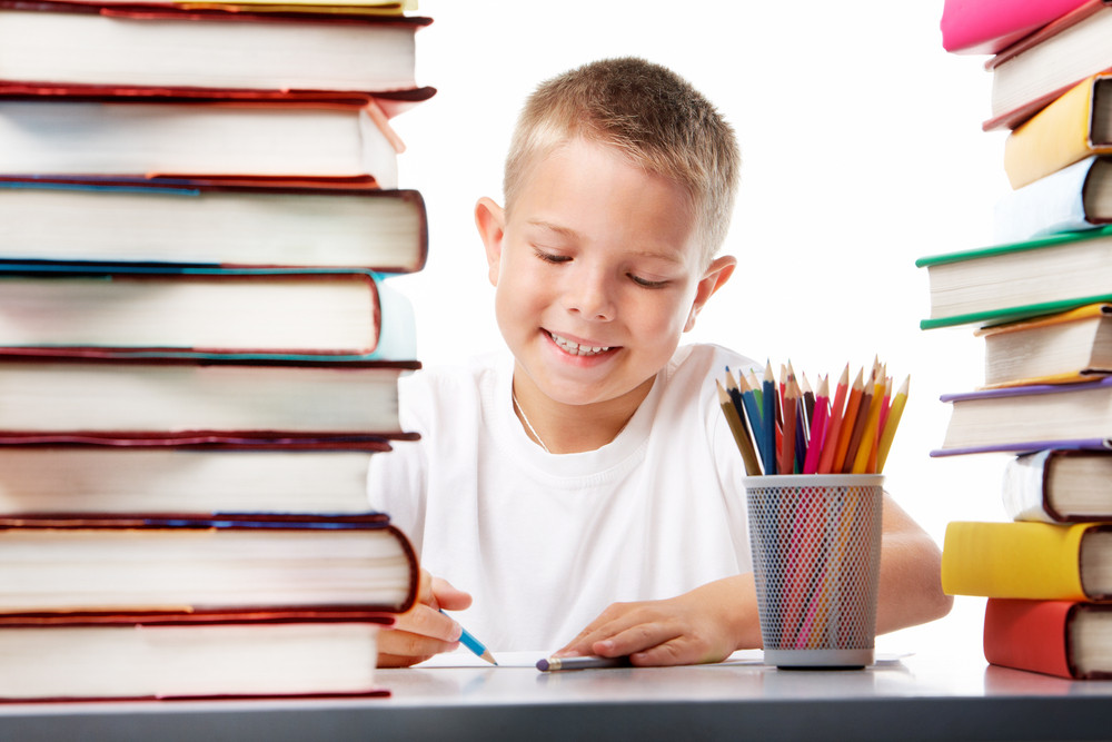 Portrait Of Cute Youngster Sitting Among Stacks Of Literature And Drawing