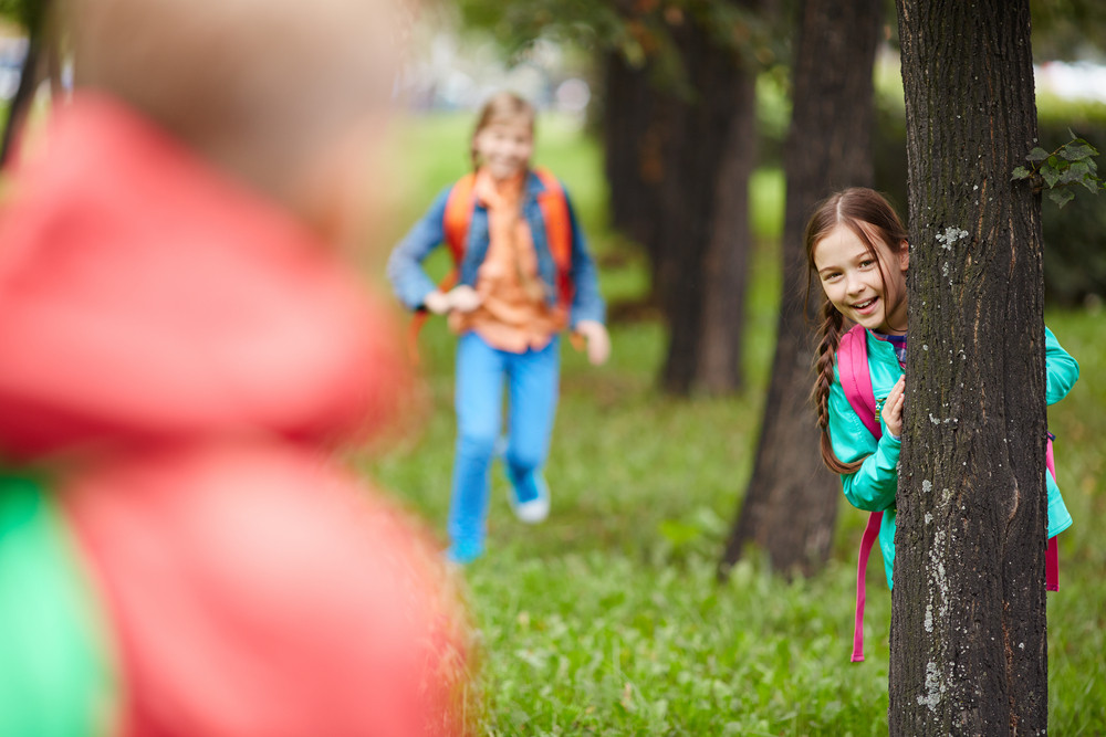 Little Girl Standing By A Tree In Park And Looking At Camera