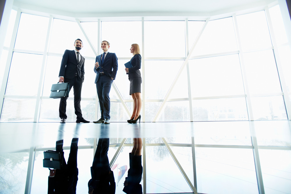 Three Successful Business Partners Standing Against Window In Office Building