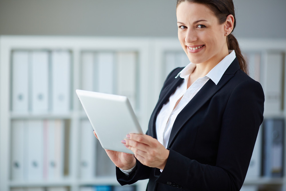 Young Businesswoman With Touchpad Looking At Camera In Office