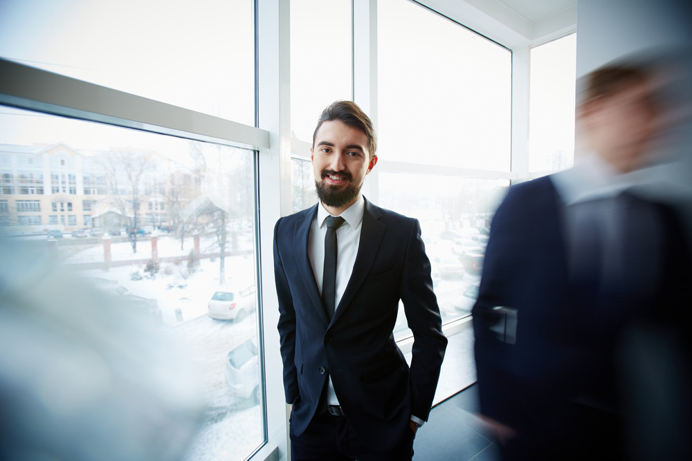 Image Of Successful Businessman Looking At Camera On Background Of Window