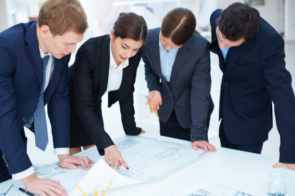 Team Of Engineers Learning Blueprint At Meeting