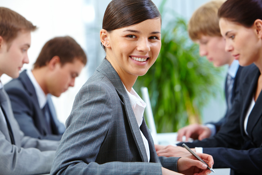 Successful Businesswoman Looking At Camera On Background Of Working Colleagues