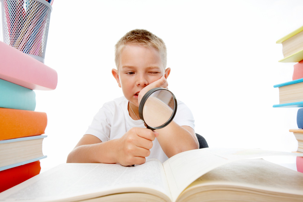 Smart Youth Reading Open Book Before Him With Serious Facial Expression