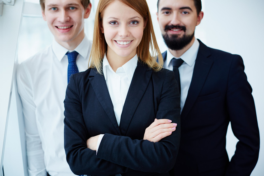 Three Successful Business Partners Looking At Camera With Smiles