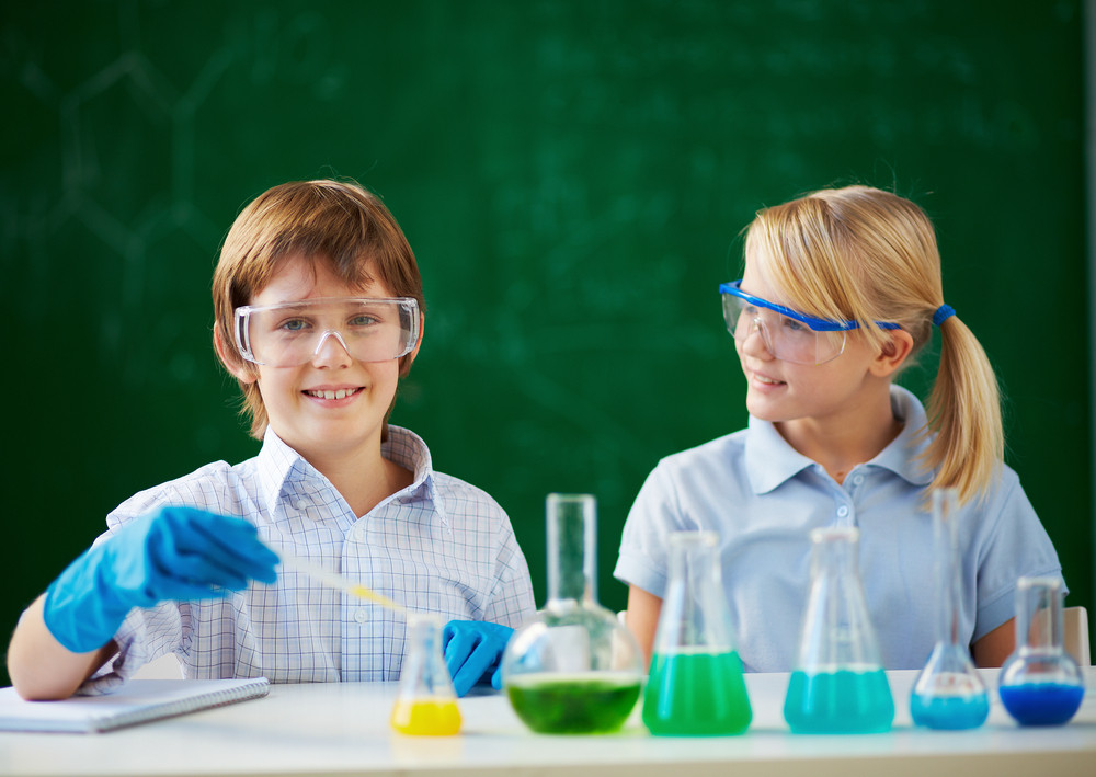 Two Schoolchildren Working With Chemical Liquids At Lesson