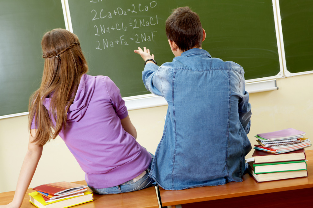 Back View Of Guy Pointing At Blackboard While Explaining Formula To Girl