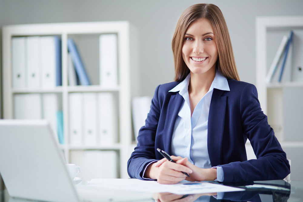Young Businesswoman Sitting At Workplace And Looking At Camera In Office