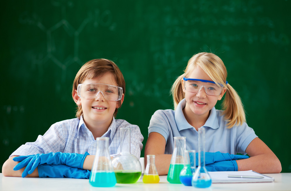 Two Schoolchildren Sitting At Lesson Of Chemistry