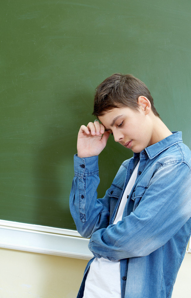 Vertical Image Of A Schoolboy Standing By The Blackboard Being Deep In Thought