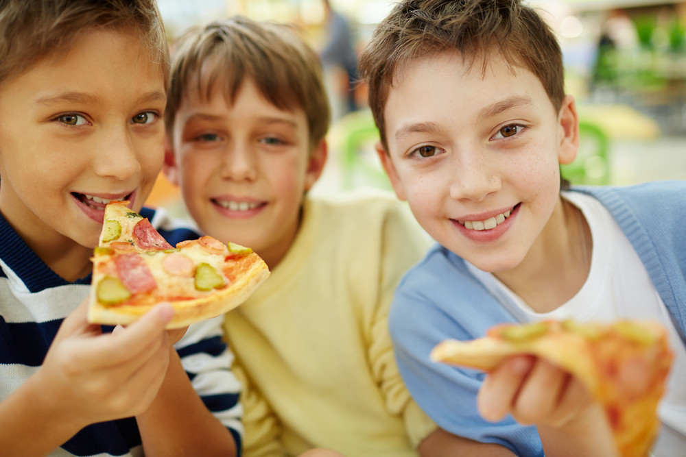 Three Happy Boys Enjoying Pizza