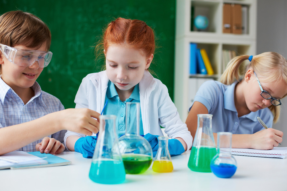 Three Children Working With Chemical Liquids At Lesson
