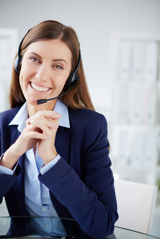 Young Businesswoman With Headset Looking At Camera With Smile