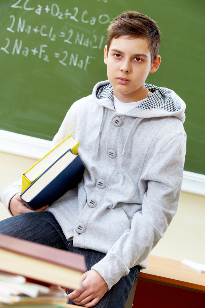 Portrait Of Smart Lad With Books Sitting In Classroom