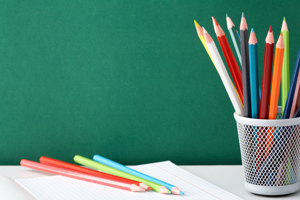 Stack Of Colorful Pencils And Open Copybook Near By On Background Of Blackboard