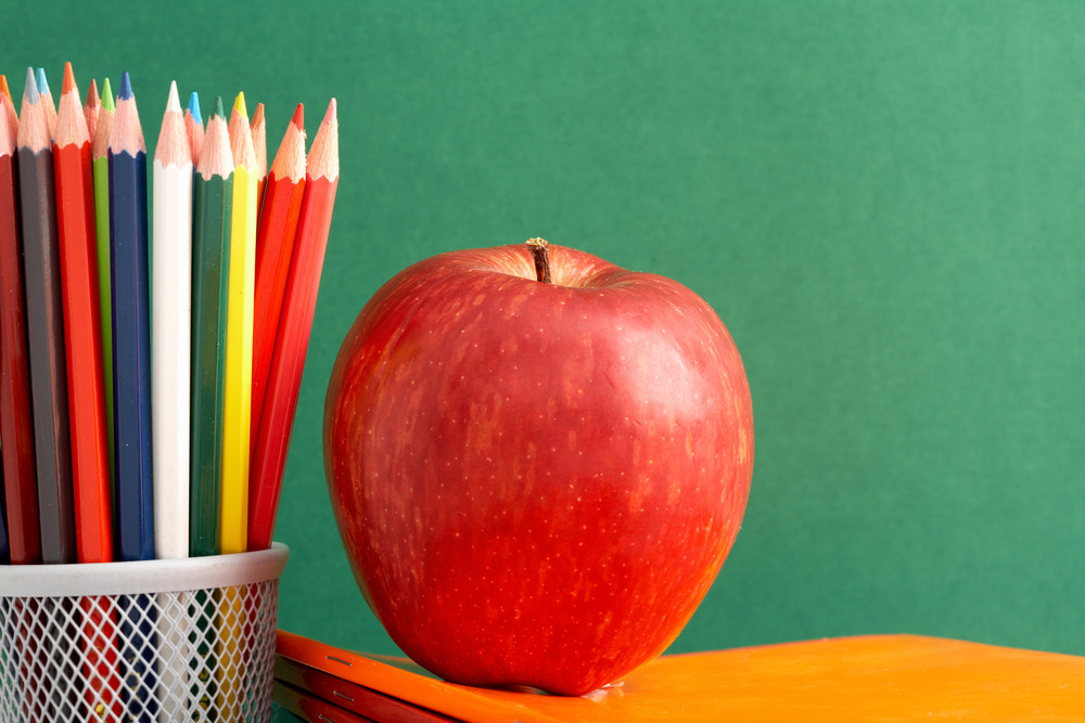 Close-up Of Big Red Apple On Stack Of Copybooks With Colorful Pencils Near By