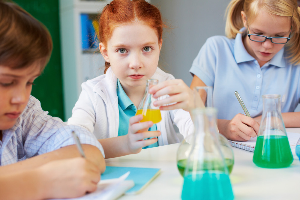 Three Children Working With Chemical Liquids At Lesson In School Lab