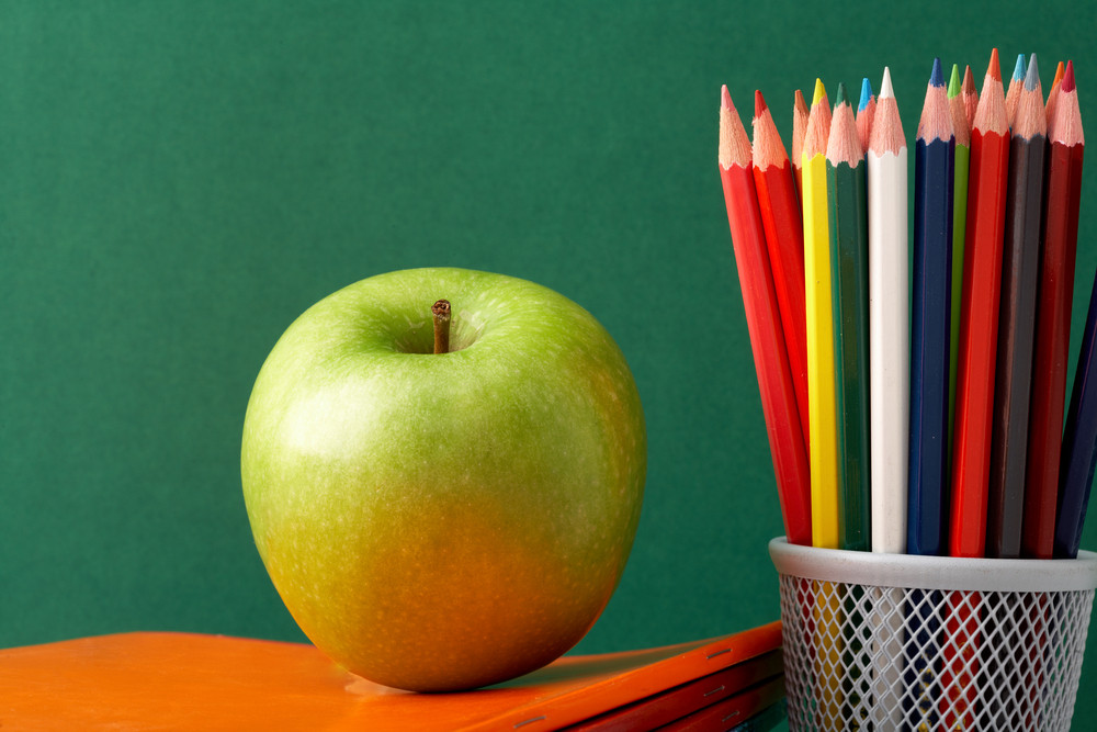 Close-up Of Big Green Apple On Stack Of Copybooks With Colorful Pencils Near By