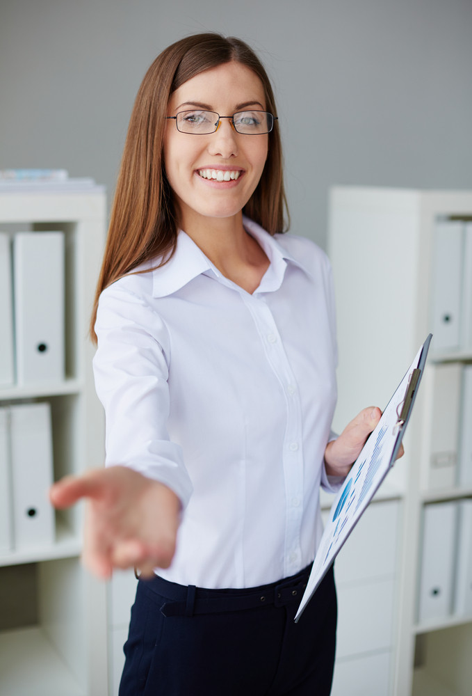Young Businesswoman With Document Looking At Camera And Welcoming You