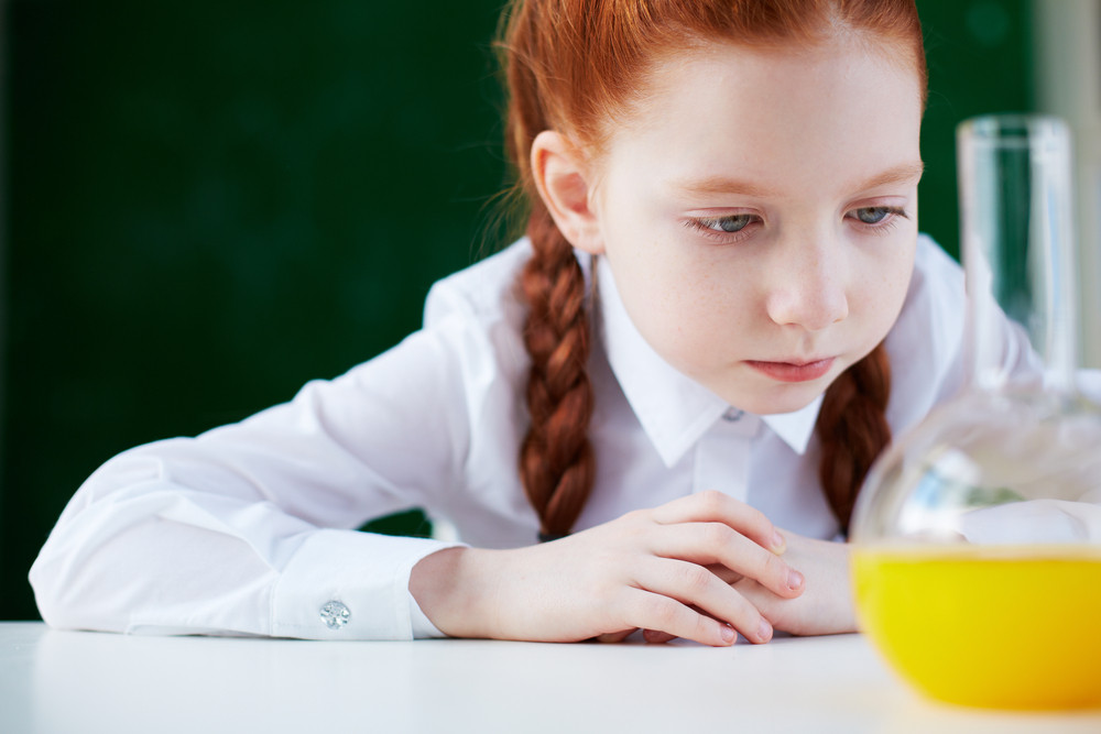 Portrait Of Serious Schoolgirl Sitting At Workplace And Looking At Chemical Liquid In Tube