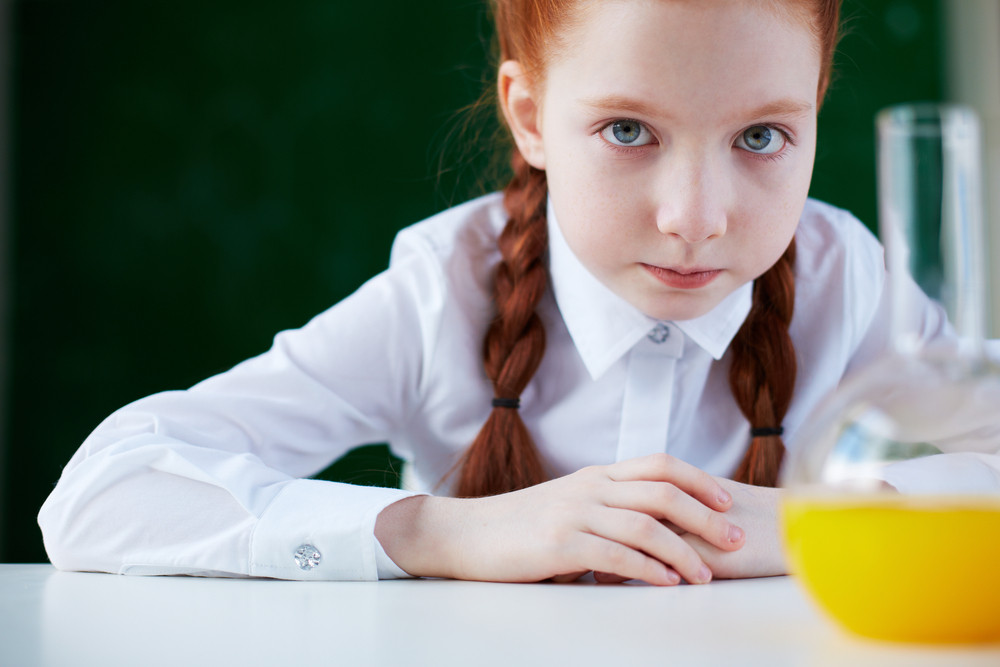 Portrait Of Schoolgirl Sitting At Workplace And Looking At Camera With Chemical Liquid In Front
