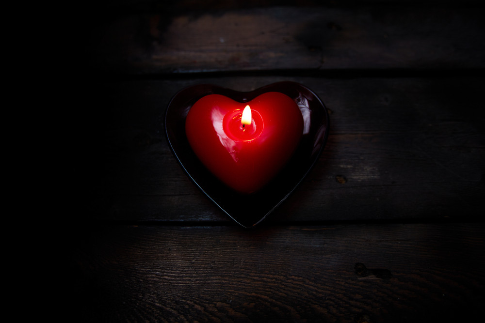 Image Of Red Heart Shaped Candle Burning On Wooden Background