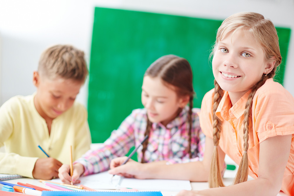 Pretty Schoolchild Looking At Camera At Lesson Of Drawing With Other Schoolkids On Background