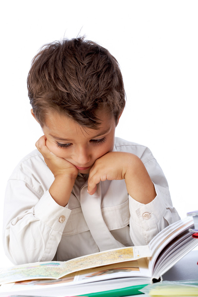 Vertical Image Of Interested Schoolkid Reading Book In Isolation