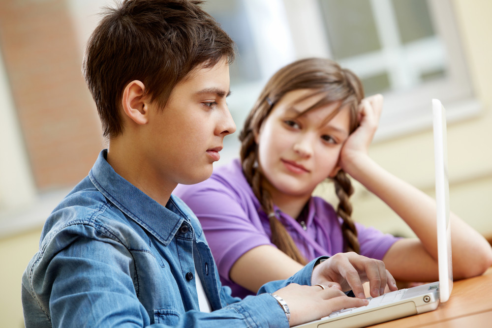 Portrait Of Teenage Girl Looking At Typing Guy At Lesson