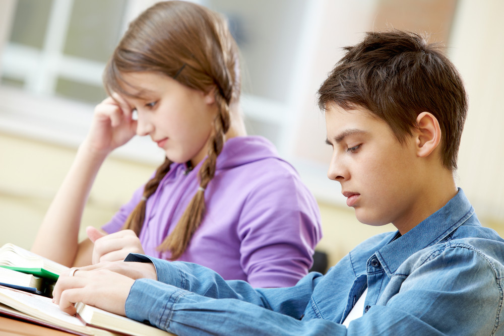 Portrait Of Teenage Boy Reading Book With His Classmate At Background