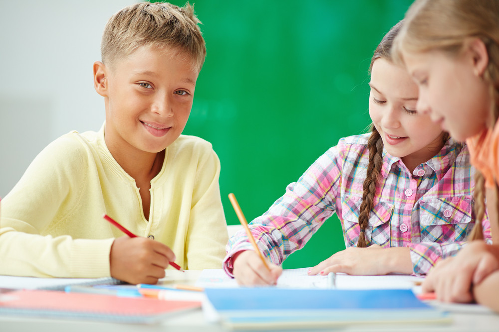 Clever Schoolboy Looking At Camera At Lesson Of Drawing With Two Girls Near By