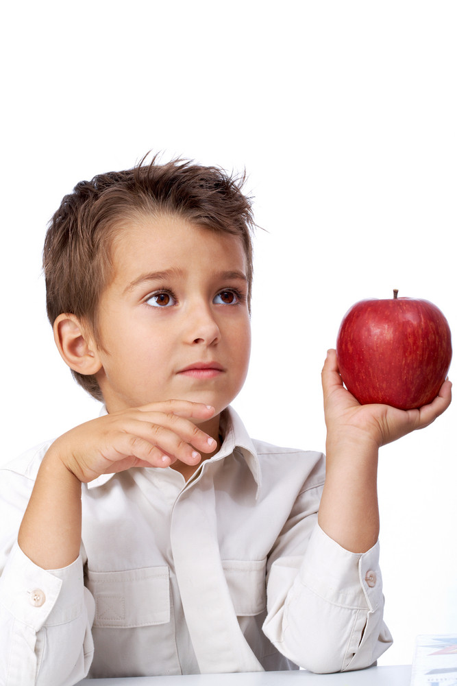 Photo Of Cute Kid Sitting At The Table With Red Apple And Looking Aside