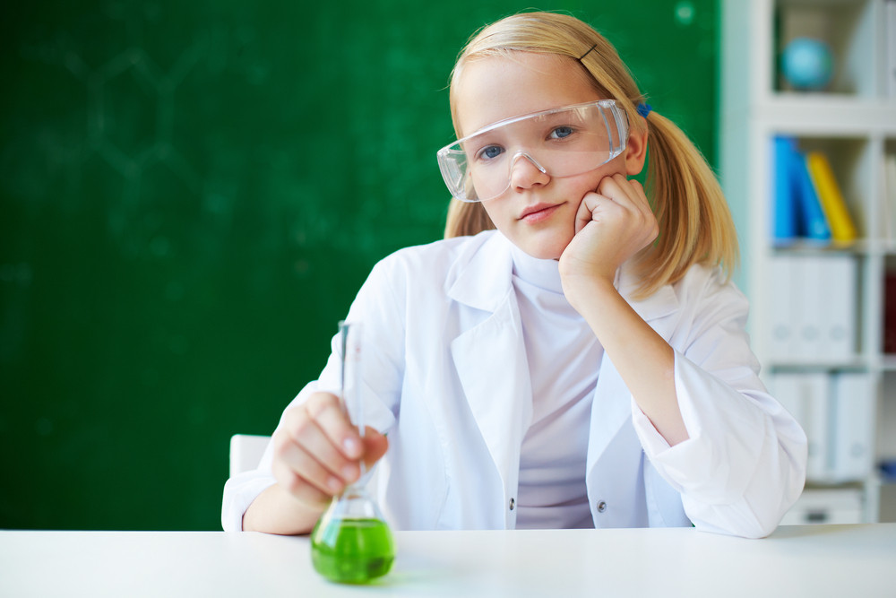 Portrait Of Cute Schoolgirl Sitting At Workplace With Chemical Liquid In Front