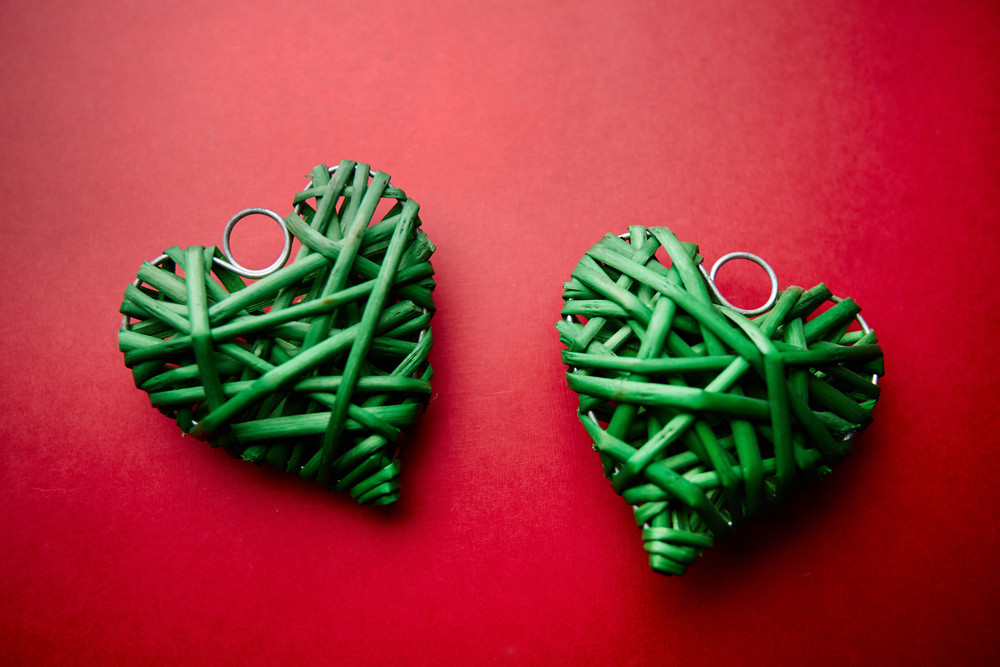 Image Of Two Decorative Green Wattled Hearts On Red Background