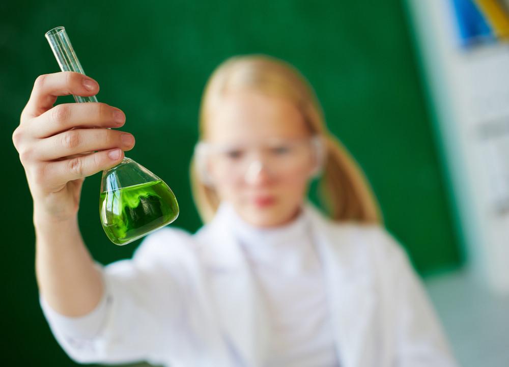 Image Of Flasks With Green Liquid Held By Schoolgirl