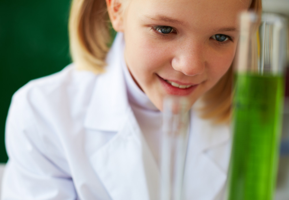 Portrait Of Cute Schoolgirl Studying Chemical Liquid In Laboratory
