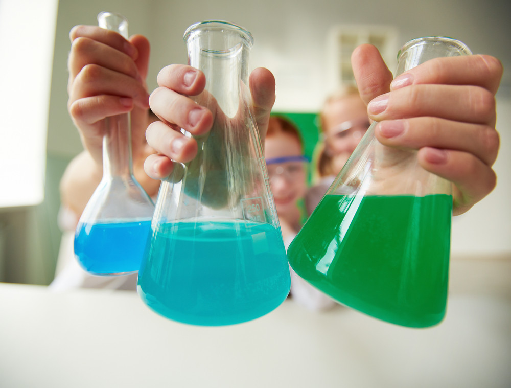 Three Tubes With Chemical Liquids Held By Schoolchildren