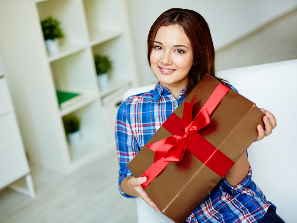 Happy Girl In Casual Clothes Holding Giftbox And Looking At Camera With Smile