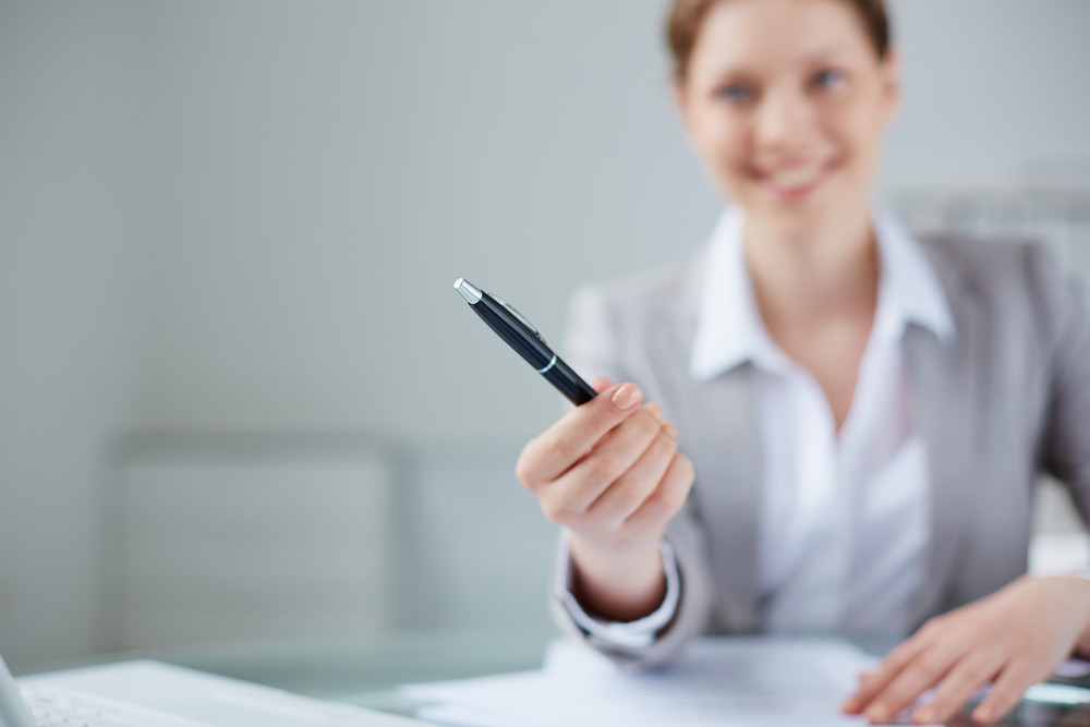 Young Businesswoman Giving Pen To Somebody