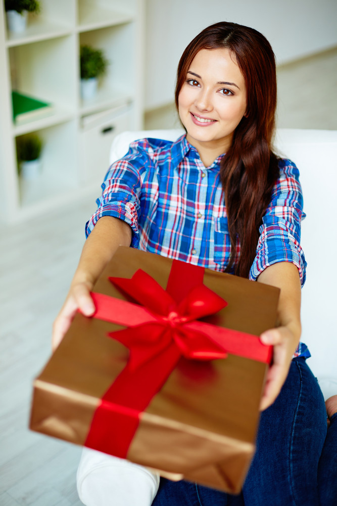 Happy Girl In Casual Clothes Giving Present And Looking At Camera With Smile